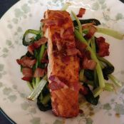 Baked salmon with bacon on a bed of tatsoi
